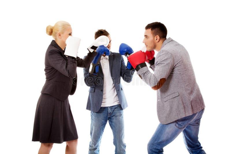 Tre genti di affari che indossano lotta della concorrenza di inizio dei guantoni da pugile immagini stock