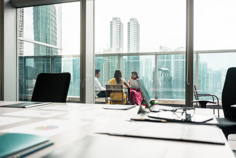 Tre genti di affari indiane che parlano durante la pausa sul lavoro fotografia stock