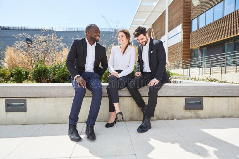 Tre genti di affari nella rottura alla chiacchierata fotografia stock