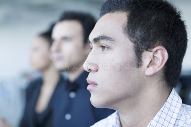 Tre genti di affari serie che si siedono in una riunione d'affari fotografia stock