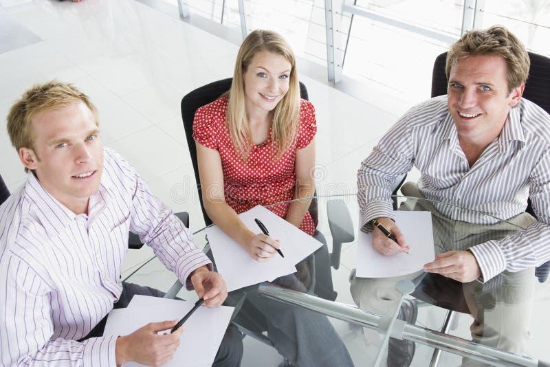 Tre genti di affari in una sala del consiglio fotografie stock