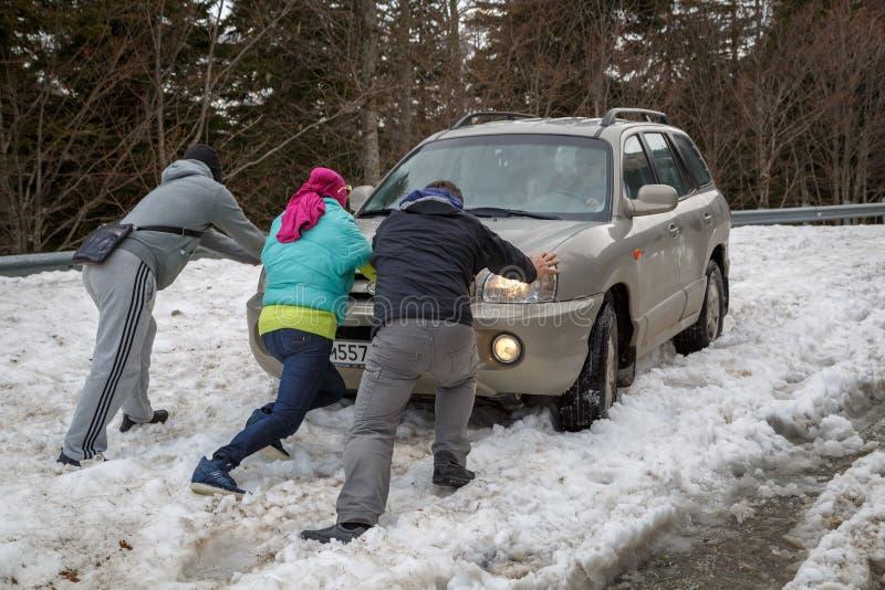 Tre genti spingono un'automobile che è attaccata in neve profonda fotografie stock libere da diritti