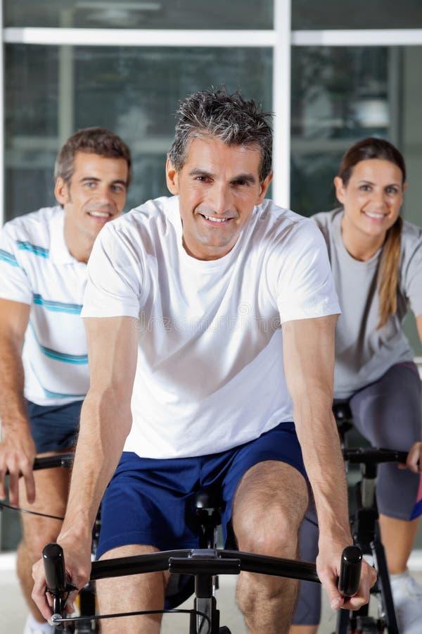 Tre genti sulle bici di esercizio fotografia stock