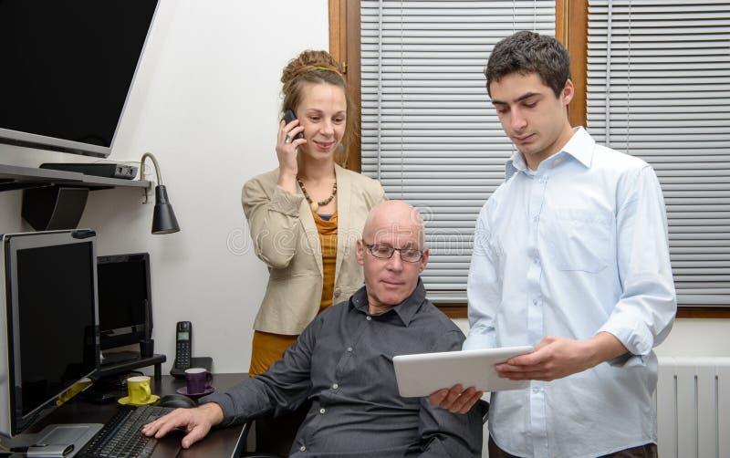 Tre genti in un ufficio fotografia stock libera da diritti