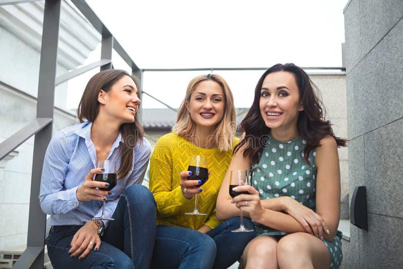 Tre giovane donna felice che ride, vino rosso bevente, divertendosi fotografie stock