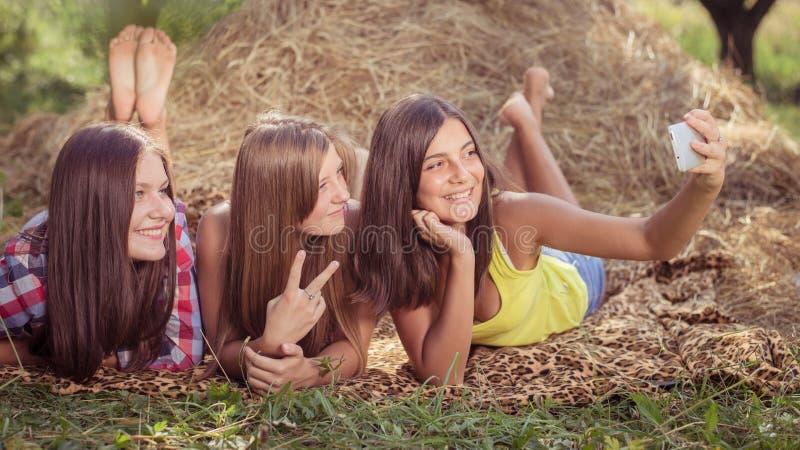 Tre giovani amiche felici che fanno selfie dal telefono fotografie stock