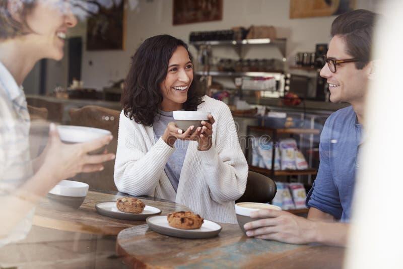 Tre giovani amici adulti che parlano, caffè bevente al caffè fotografia stock libera da diritti