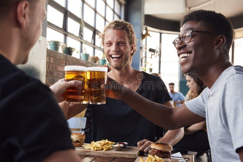 Tre giovani amici maschii che si incontrano per le bevande ed alimento che produce un pane tostato in ristorante fotografia stock