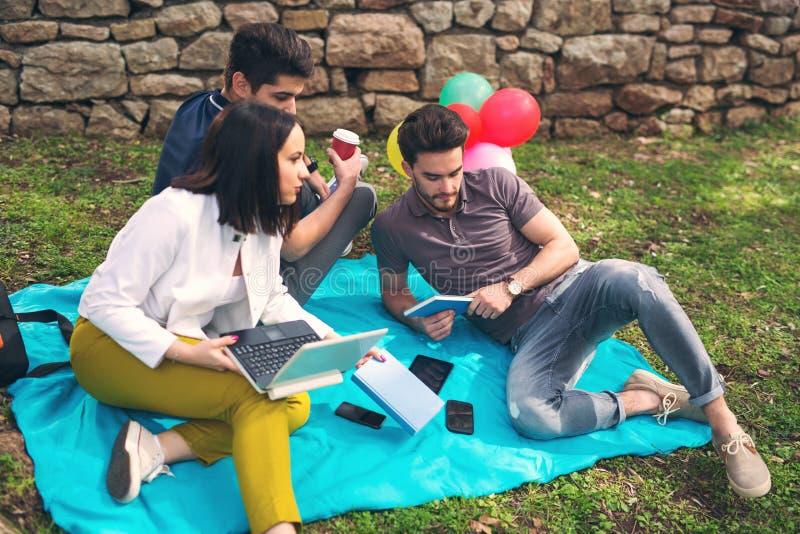 Tre giovani amici sul picnic fotografia stock