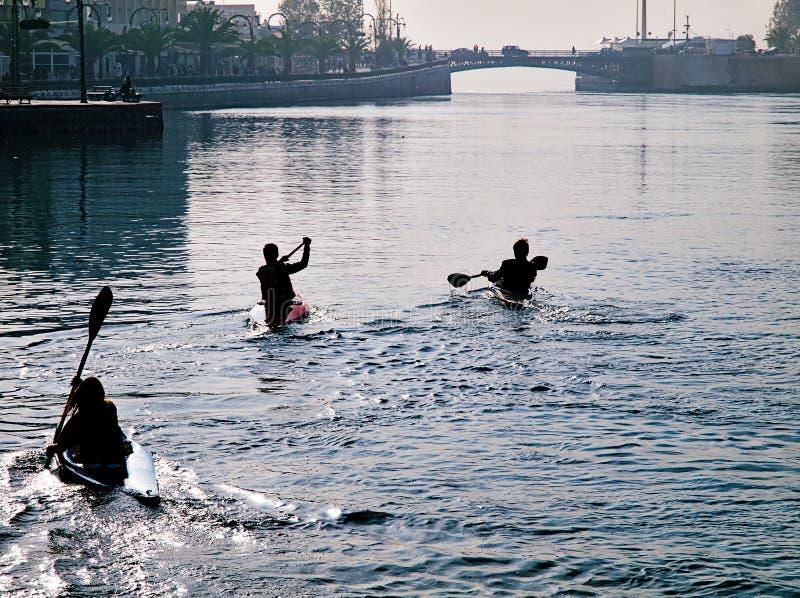 Tre giovani atleti che si preparano sulla canoa immagini stock