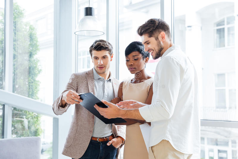 Tre giovani che discutono insieme business plan nell'ufficio immagine stock libera da diritti