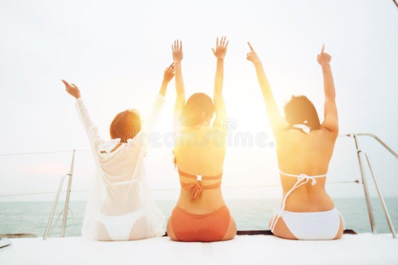 Tre giovani donne allegre in bikini che si siede sulla barca e che ammira vista del mare immagine stock