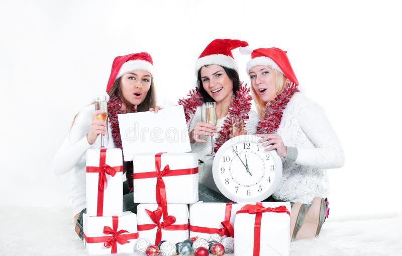 Tre giovani donne in cappelli di Santa Claus con i regali f di Natale fotografia stock libera da diritti