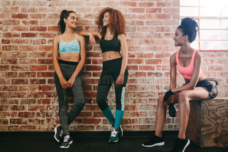 Tre giovani donne che riposano dopo l'esercizio in palestra fotografie stock