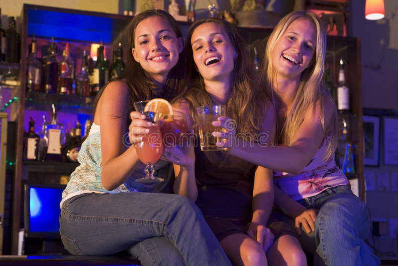 Tre giovani donne che si siedono su un contatore della barra immagine stock