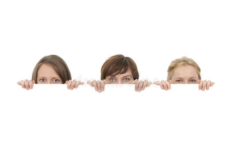 Tre giovani donne dietro un annuncio in bianco della bandiera fotografia stock libera da diritti