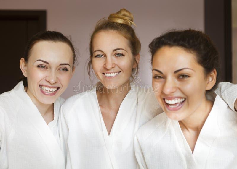 Tre giovani donne felici alla località di soggiorno di stazione termale fotografie stock libere da diritti