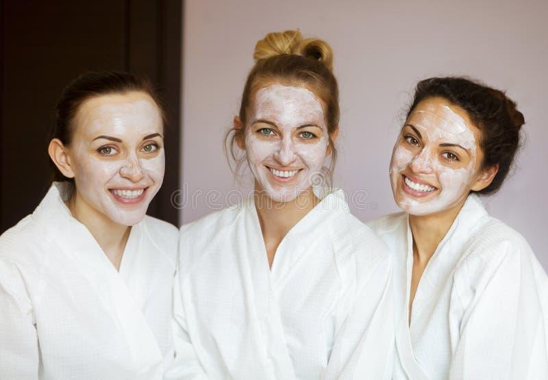 Tre giovani donne felici alla località di soggiorno di stazione termale immagini stock libere da diritti