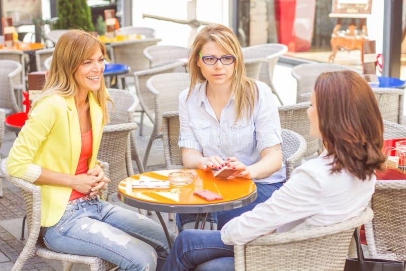 Tre giovani donne hanno pausa caffè fotografie stock