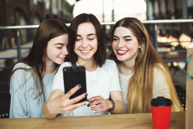 Tre giovani donne si divertono insieme e prendono il selfie immagine stock