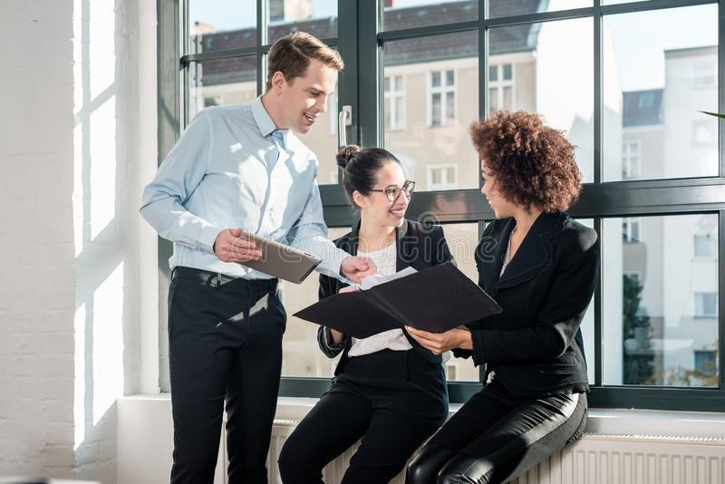 Tre giovani impiegati allegri che sorridono in un ufficio moderno immagini stock libere da diritti