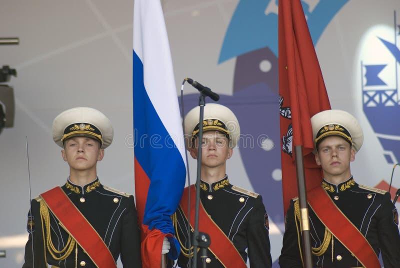 Tre giovani militari tengono le bandiere della Russia e di Mosca immagine stock