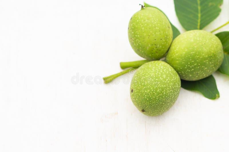 Tre giovani noci verdi con le foglie isolate su fondo bianco e verde Alimento vegetariano fotografia stock