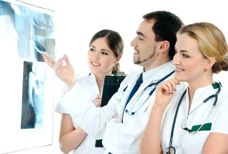 Tre giovani operai medici che esaminano i raggi X immagine stock