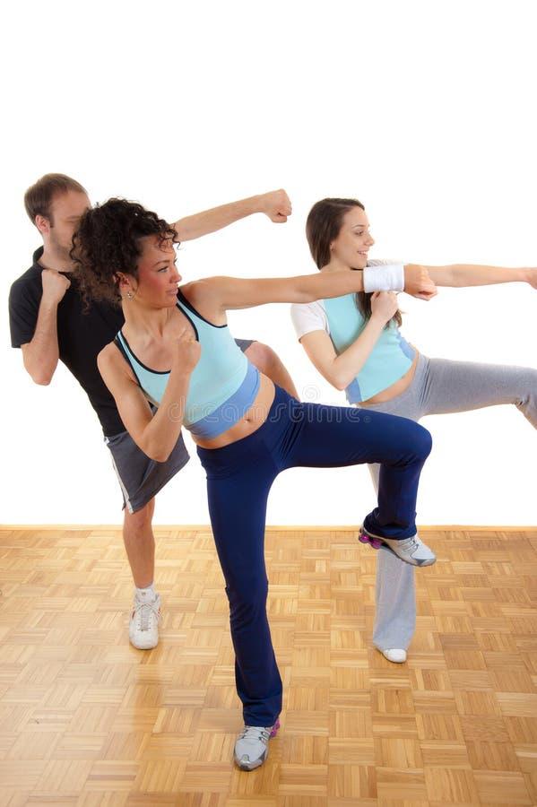 Tre giovani raggruppano l'addestramento di forma fisica immagine stock libera da diritti