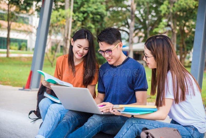 Tre giovani studenti asiatici della città universitaria godono del fischio della lettura e di ripetizioni immagine stock libera da diritti