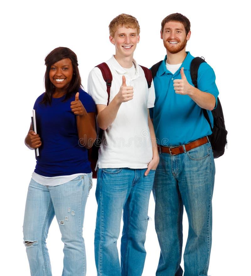 Tre giovani studenti di college che mostrano i pollici aumentano il segno fotografie stock