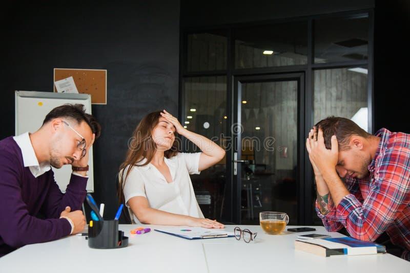 Tre giovani uomini d'affari hanno emicrania all'ufficio, guasto triste fotografia stock libera da diritti