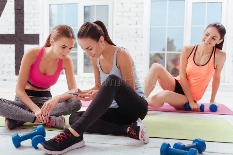 Tre gladde kvinnor som kopplar av efter genomkörare i idrottshall royaltyfri bild