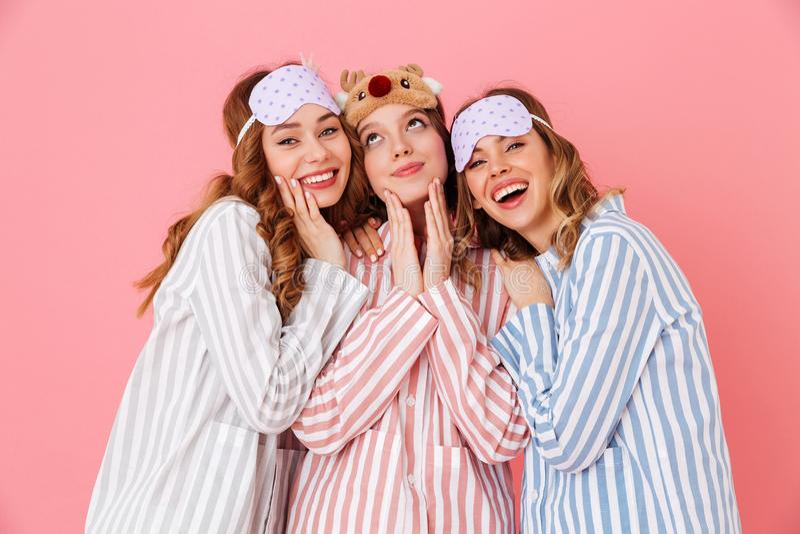 Tre glade flickvän20-tal som bär fritidkläder och sömn royaltyfri foto