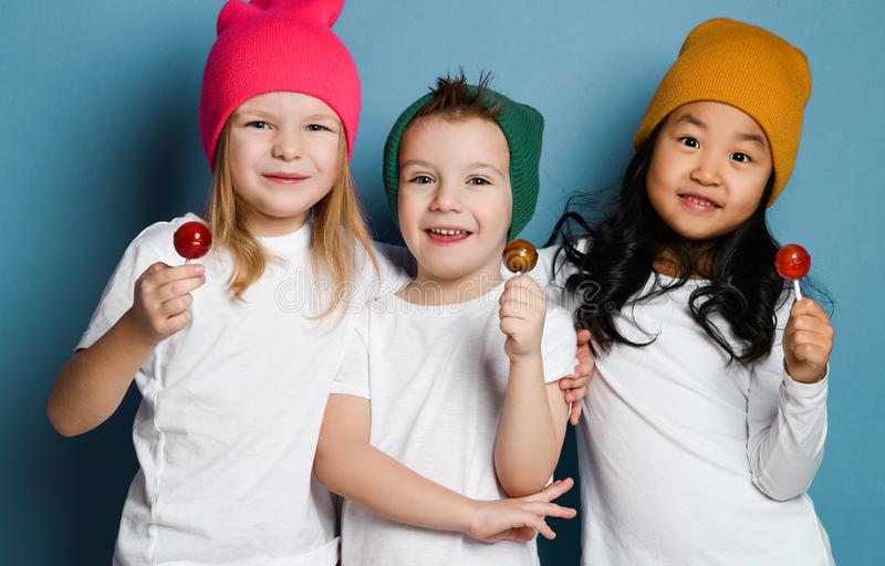 Tre glade vänungar i vita t-skjortor och färgrika hattar rymmer lyckligt le krama för söta klubbagodisar fotografering för bildbyråer