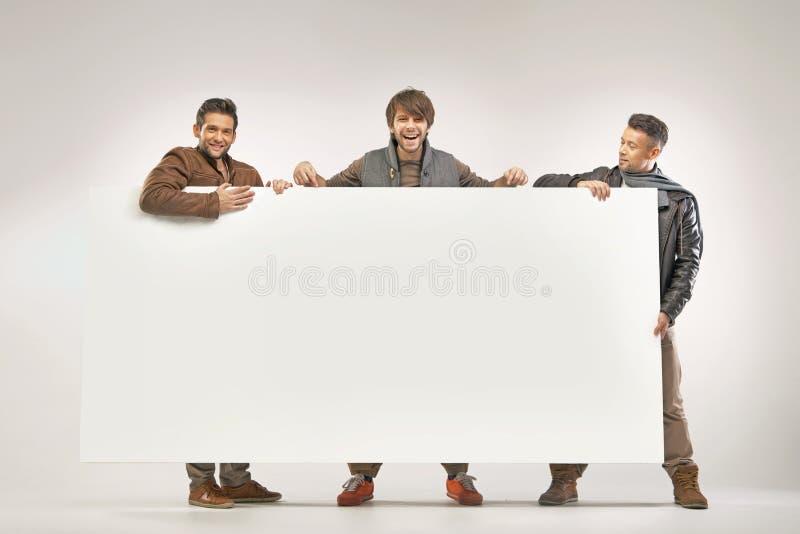Tre gladlynta grabbar som rymmer brädet royaltyfri bild