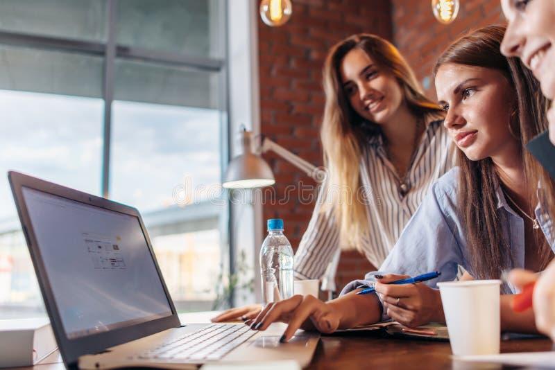 Tre gladlynta kvinnliga högskolestudenter som surfar internet genom att använda bärbara datorn som söker tillsammans informatione royaltyfria foton
