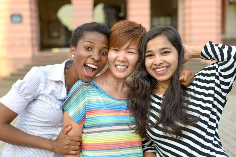 Tre gladlynta mångkulturella kvinnor som tillsammans poserar fotografering för bildbyråer
