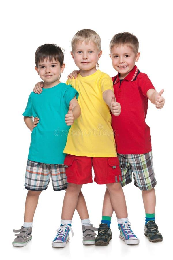 Tre gladlynta pojkar rymmer upp hans tummar arkivbild