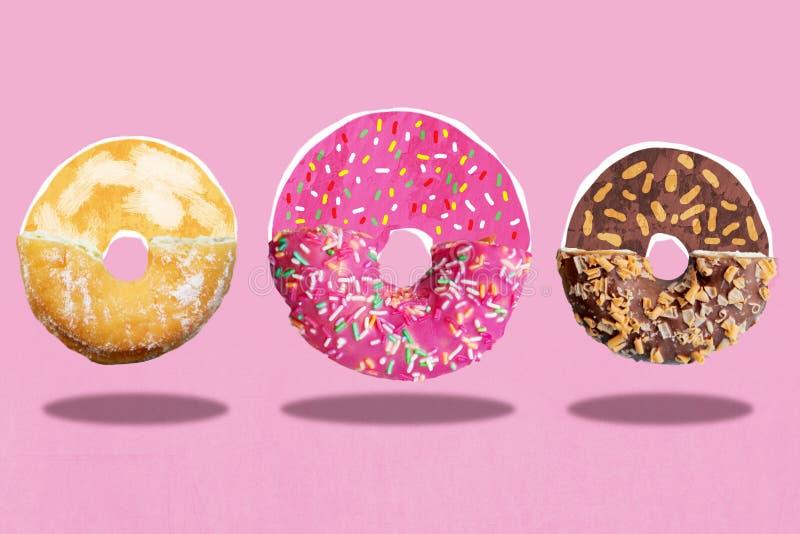 Tre glasade donuts, kräm, choklad och rosa klipps och den drog flugan i luft royaltyfri illustrationer