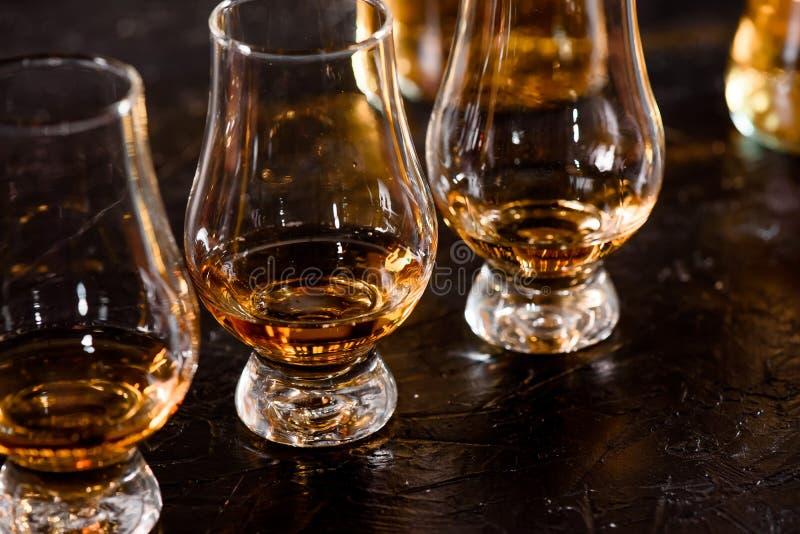 Tre Glencairn exponeringsglas med whisky på stångett träräknareslut upp på bakgrunden av oskarpa flaskor royaltyfria foton