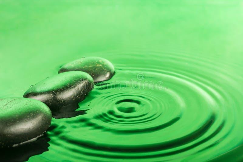 Tre gocce di pietra della stazione termale si trovano nell'acqua verde immagine stock