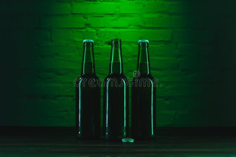 tre gröna ölflaskor nära gör grön arkivfoton