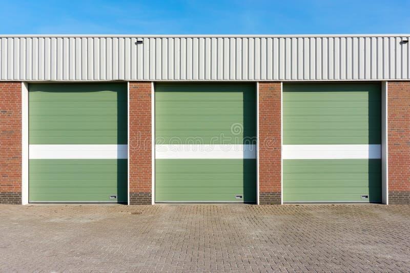 Tre gröna garagedörrar med vita band arkivfoto