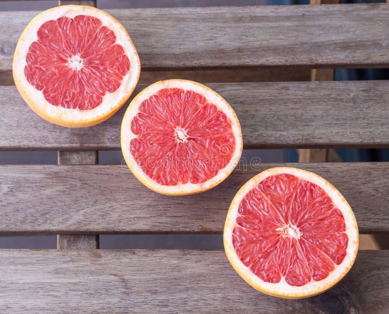Tre grapefrukthalvor på en träbakgrund arkivfoto