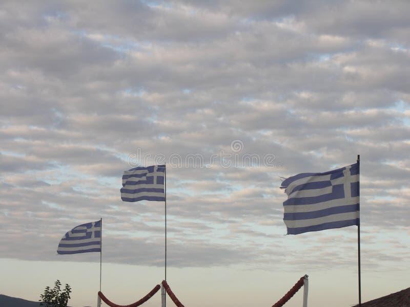 Tre grekiska flaggor framme av molnig himmel royaltyfri bild