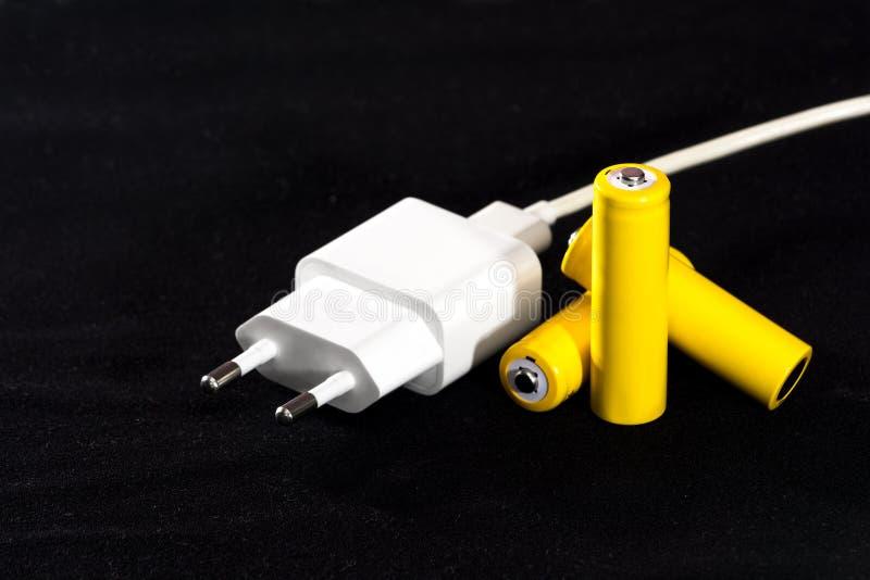 Tre gula batterier och batteriuppladdare pluggar närbild på en suddig bakgrund för mörk svart elkrafter Batteridrift Accumulato arkivbilder