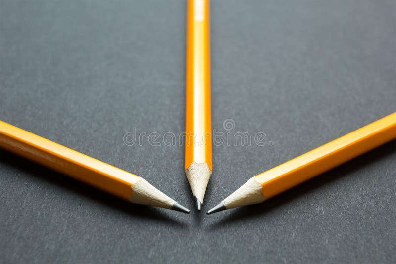 Tre gula blyertspennor på svart papper royaltyfri foto