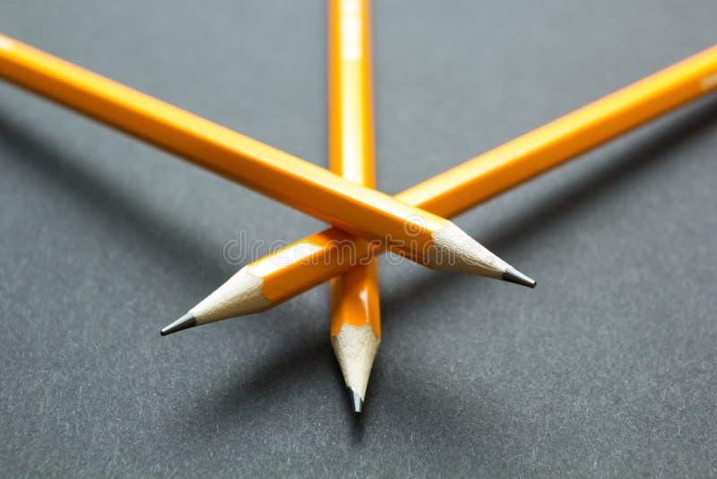 Tre gula blyertspennor på svart papper royaltyfri fotografi