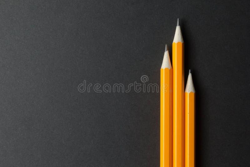 Tre gula blyertspennor på svart papper, tomt utrymme arkivfoto